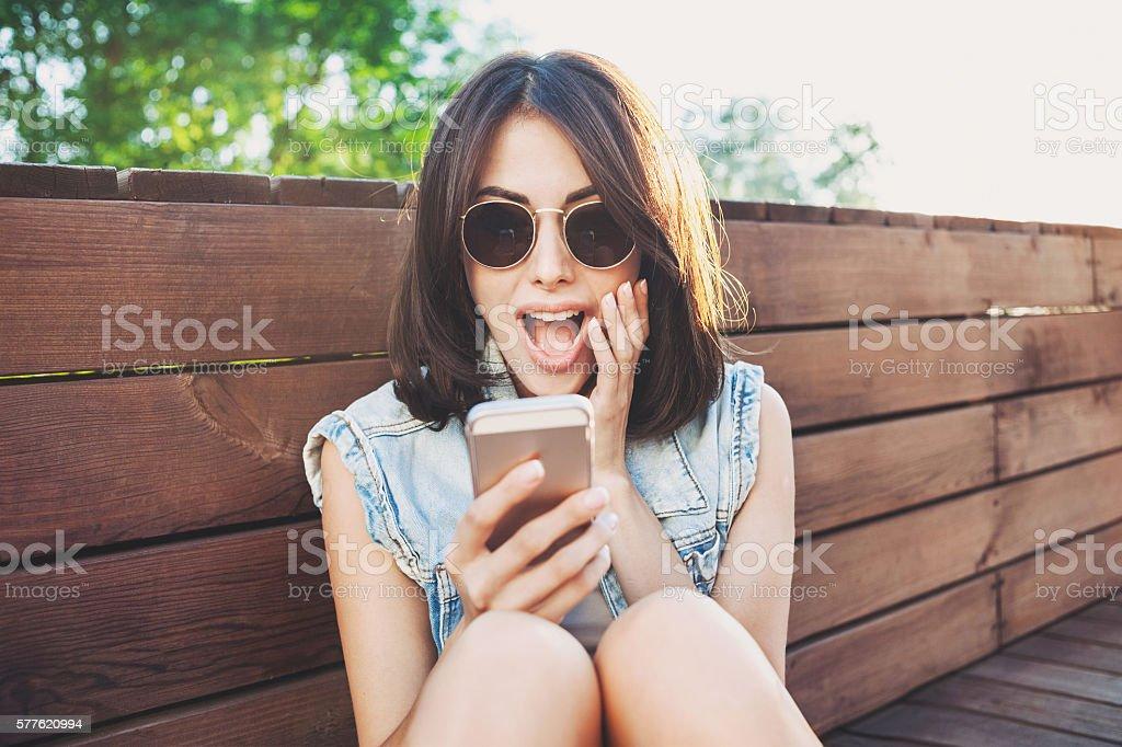 Surprised girl using smart phone royalty-free stock photo