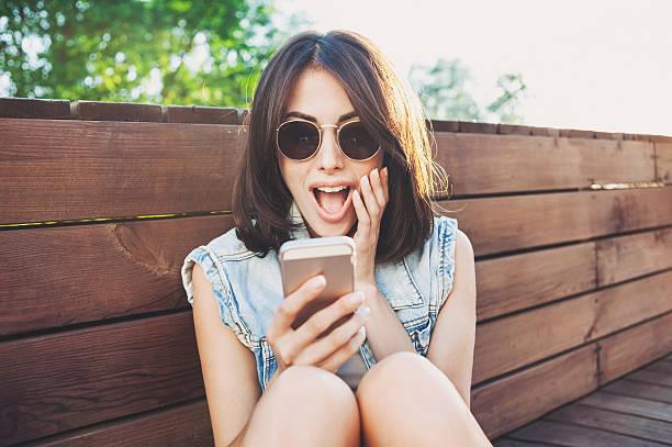 Surprised girl using smart phone stock photo