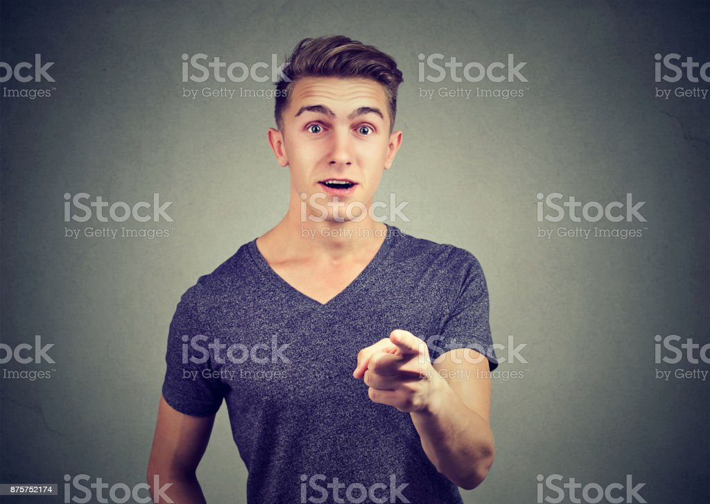 Surprised handsome young man pointing finger at camera isolated on gray background stock photo