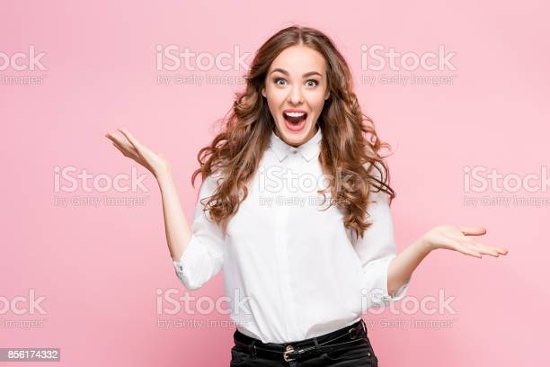 Surprised happy beautiful woman looking in excitement. Studio shot on pink background