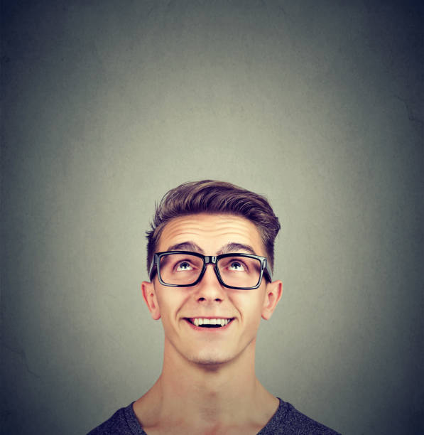 Surprised happy man wearing glasses looking up stock photo