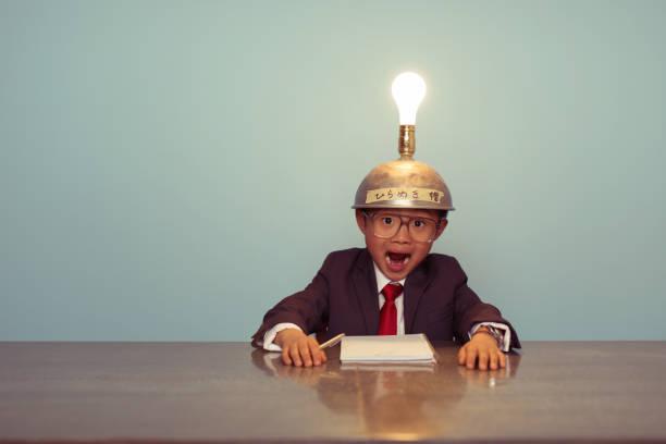 Surprised Japanese Business Boy Wearing Lit Up Thinking Cap stock photo