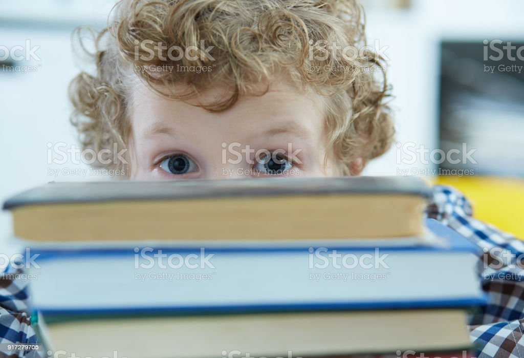 Surprised Kid hides behind the pile of books in library. stock photo