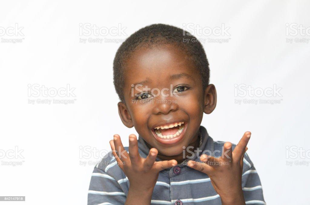 Sorpresa africano niño emocionado por conseguir un presente aislado en blanco - foto de stock