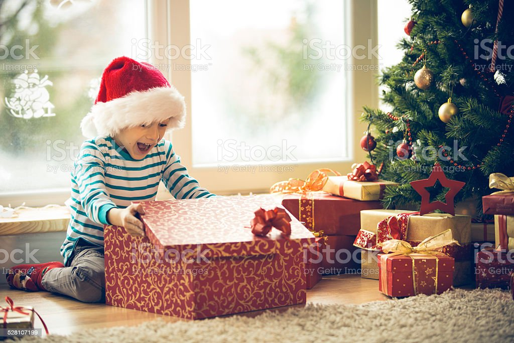 Surprised little boy opening Christmas present stock photo