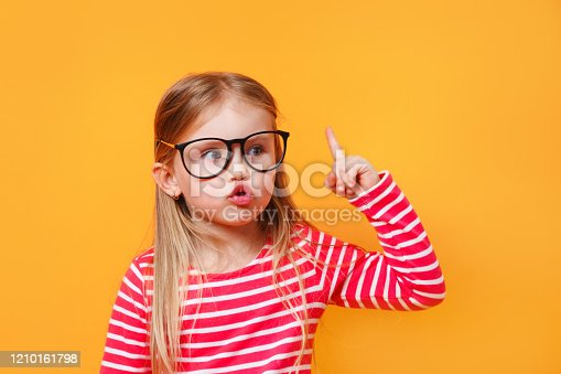 Surprised little child in glasses pointing up on yellow background