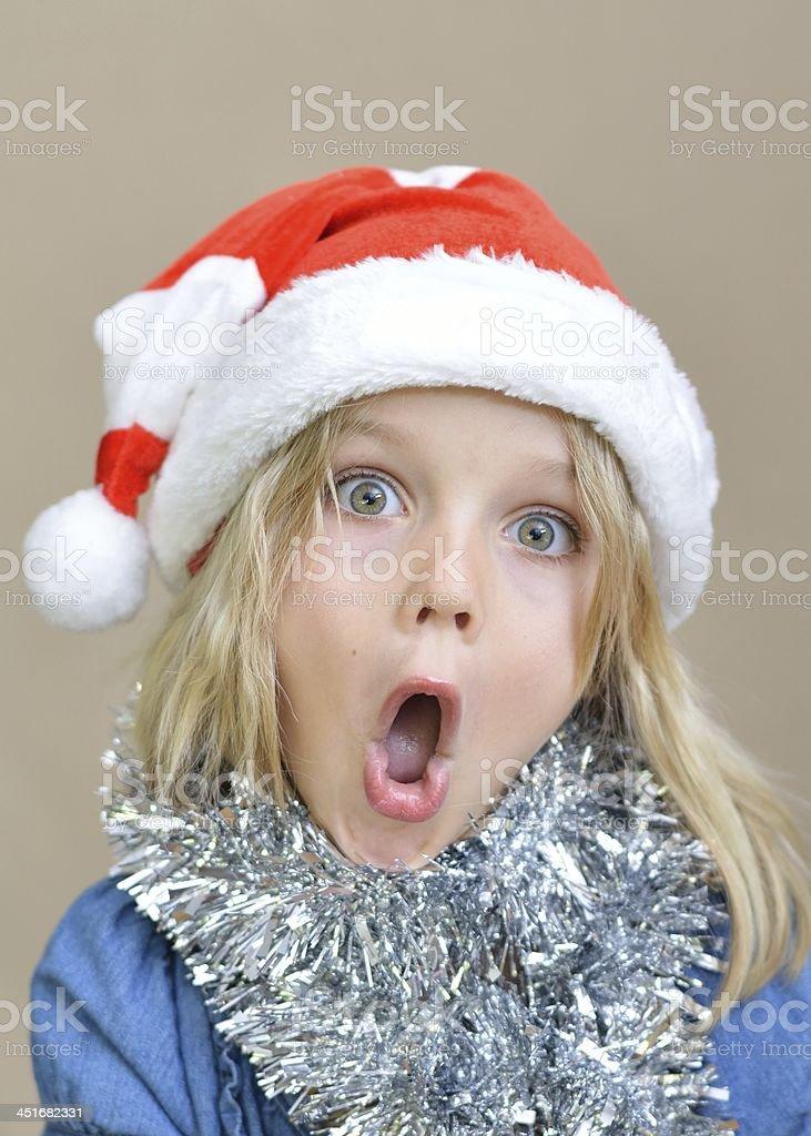 Surprised little girl in Santa hat stock photo
