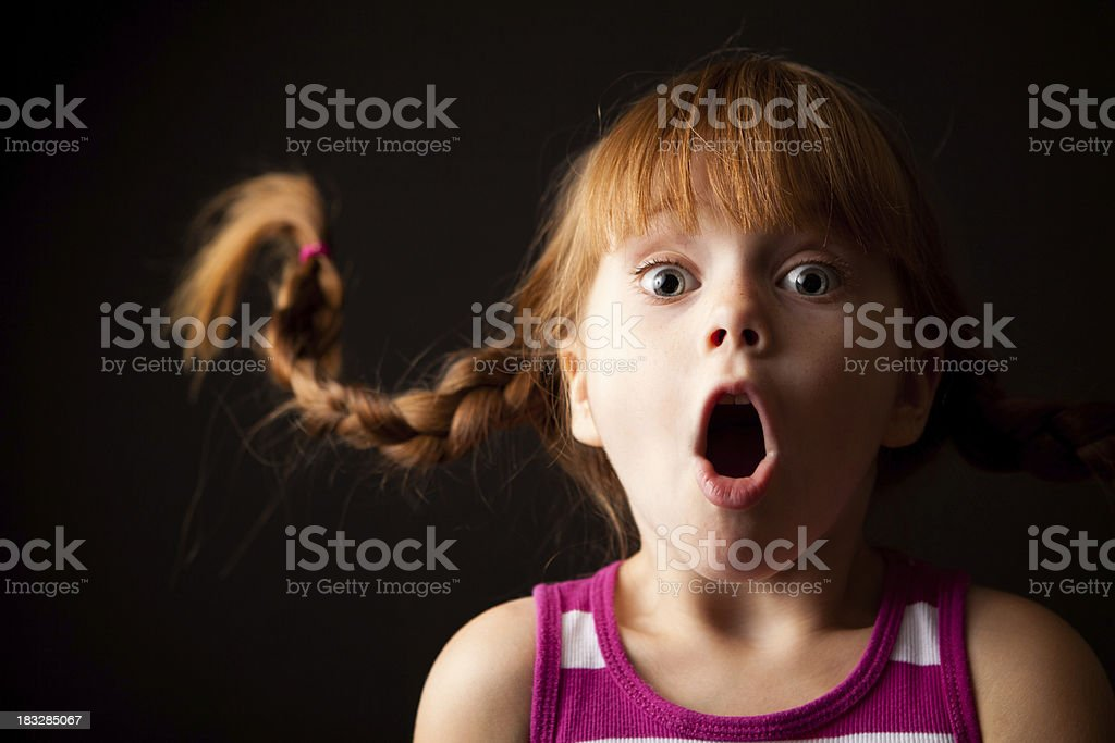 Surprised Little Girl with Upward Braids Gasping on Black Background royalty-free stock photo