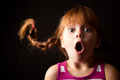 """""""Color photo of a surprised, red-haired girl with upward braids gasping on black background."""""""