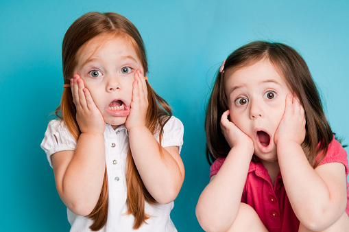 Surprised Little Girls With Looks Of Shock Stock Photo - Download Image Now