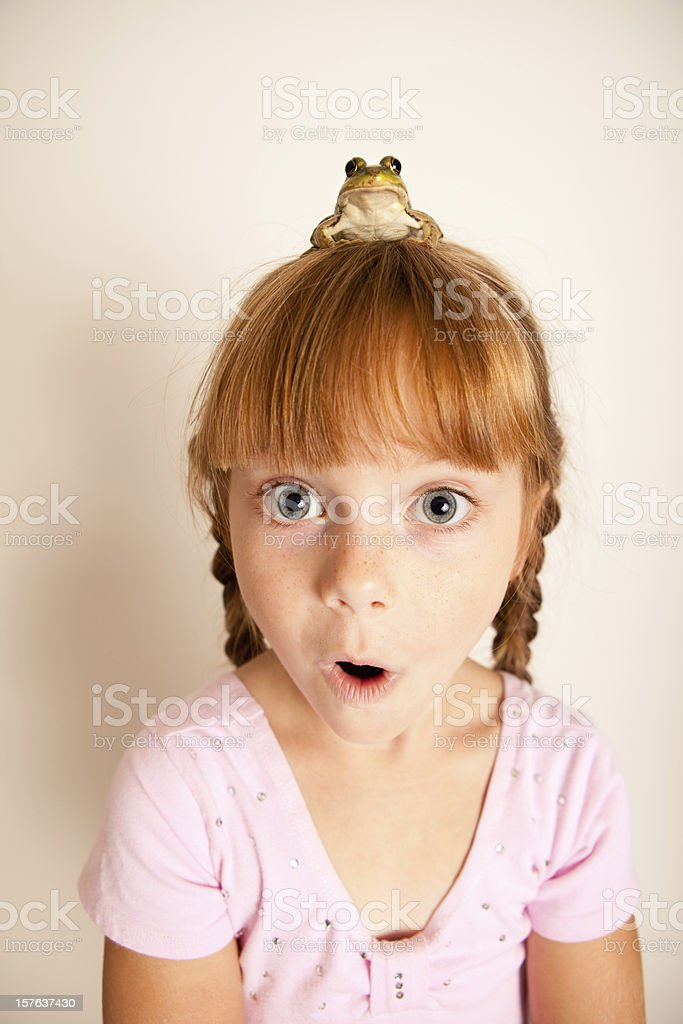 Surprised Little Princess Girl with a Frog on Her Head royalty-free stock photo
