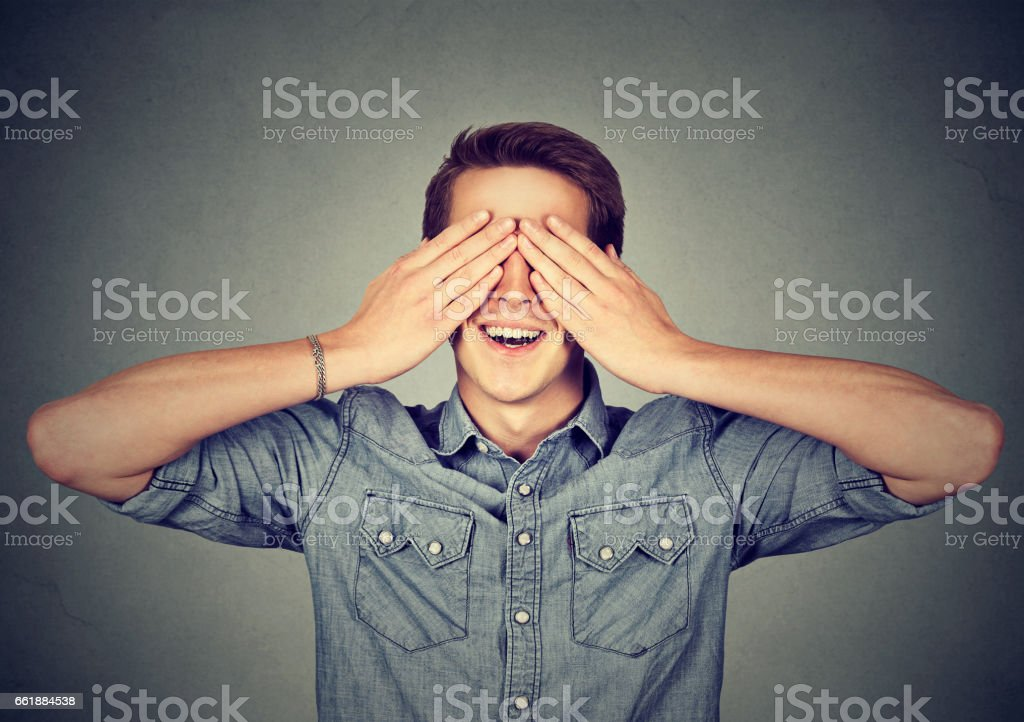 Surprised man covering his eyes with hands smiling stock photo