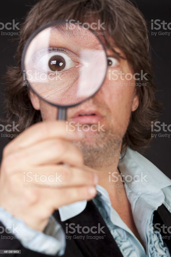 Surprised man holding a loupe royalty-free stock photo