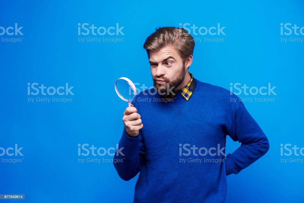 Surprised man looking through a magnifying glass stock photo
