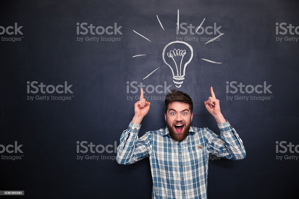 Surprised man pointing up with both hands over chalkboard background stock photo