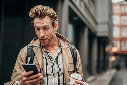One man, handsome young man on the street outdoors in city, holding disposable cup of coffee and using smart phone.