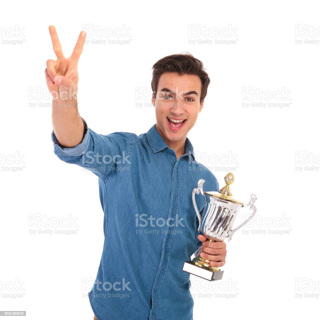 surprised  man winning  cup award and makes the victory sign stock photo