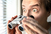 istock Surprised man with binoculars. Curious guy with big eyes. Nosy neighbour stalking or snooping secrets, gossip and rumour. Silly funny face. Shocked about unbelievable news. 1158779064