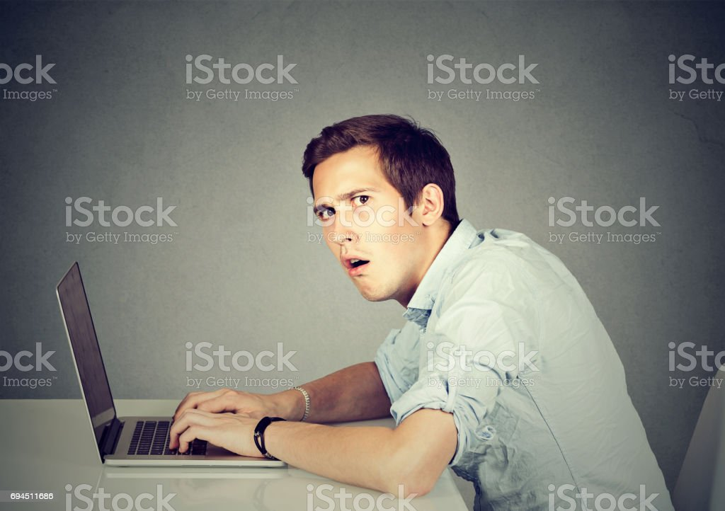 Surprised man with laptop sitting at desk stock photo