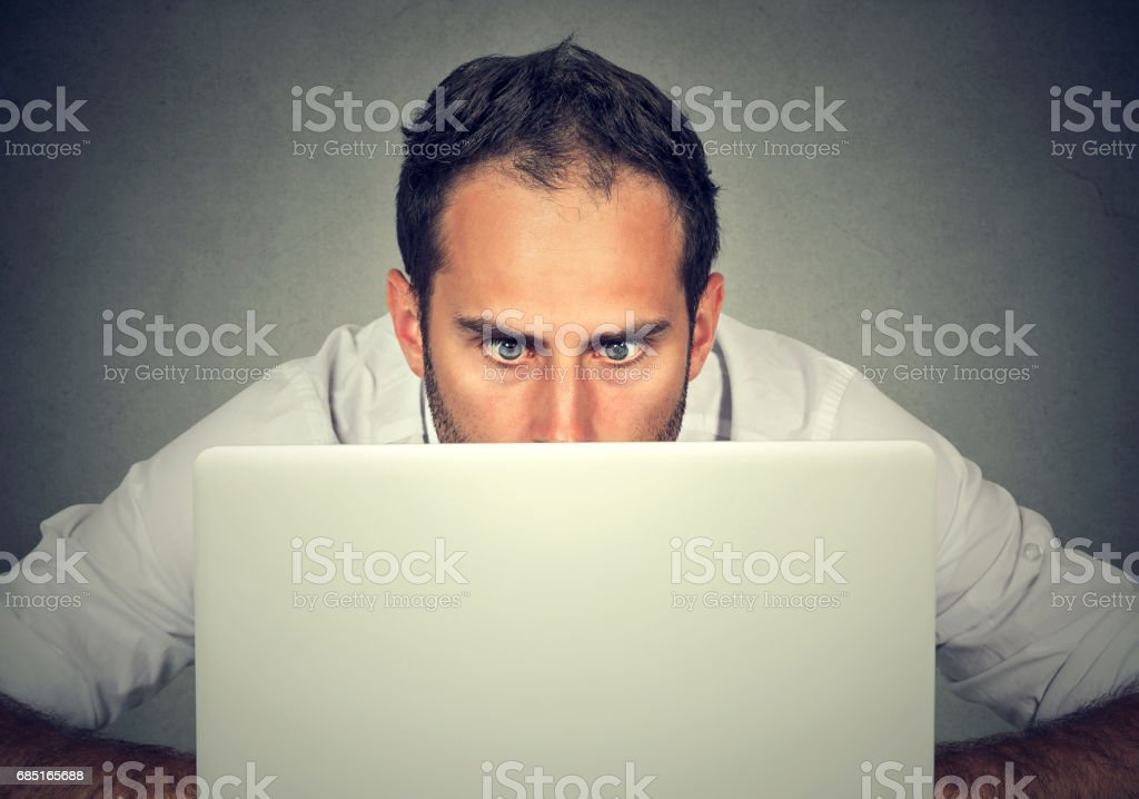 Surprised man with wide eyes hiding behind a laptop computer staring at the screen with a shocked scared face expression stock photo