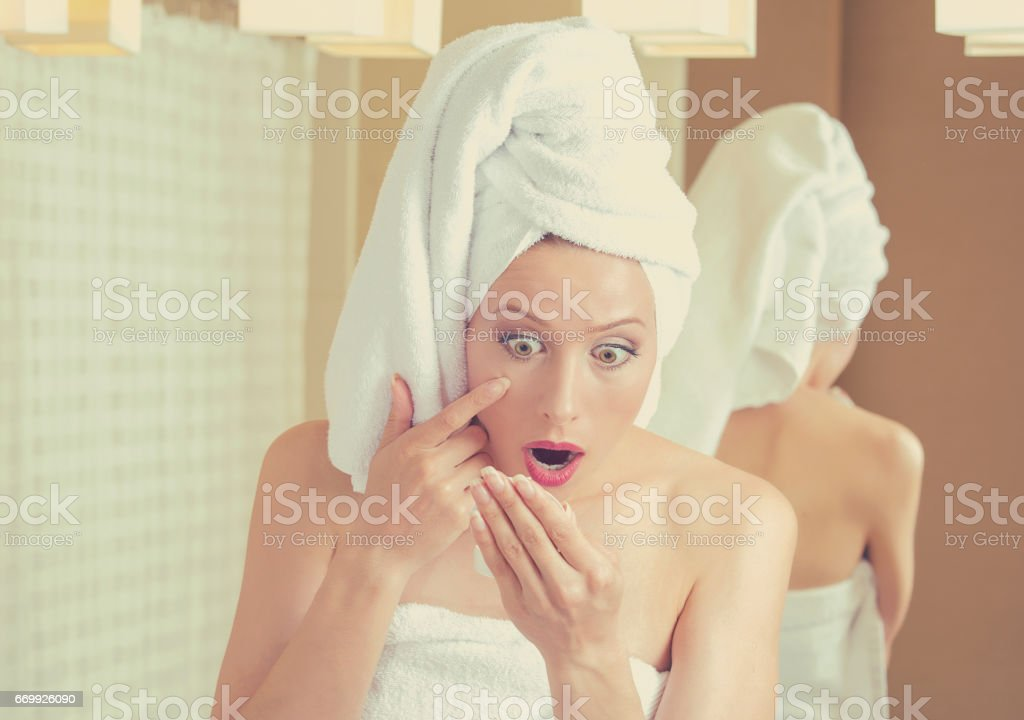surprised middle aged woman looking in a mirror unhappy with wrinkles on her face stock photo