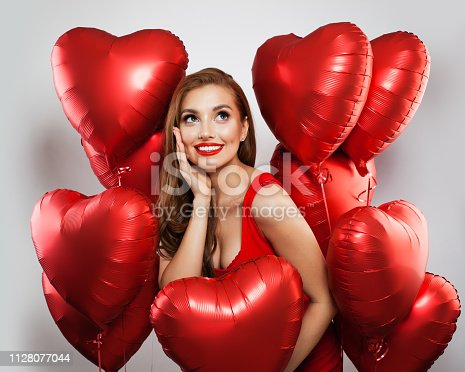 Surprised model woman with red balloons on white background. Cheerful girl with red lips makeup smiling and looking up. Surprise, gifts and Valentine's day concept