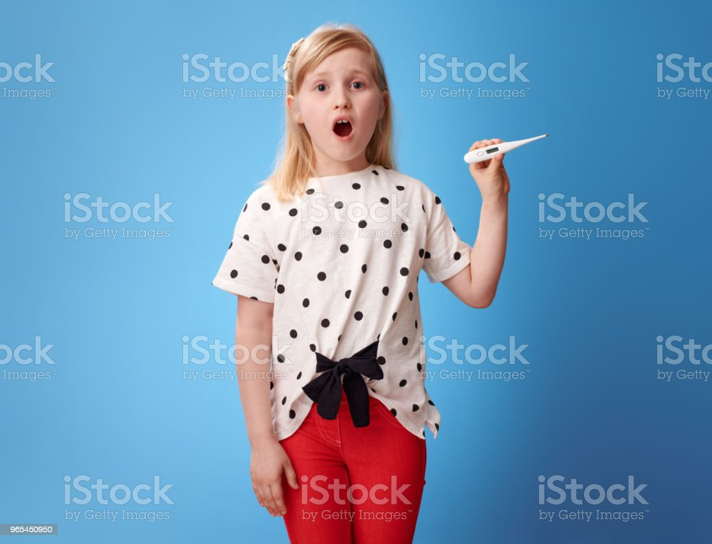 surprised modern girl in red pants on blue showing thermometer zbiór zdjęć royalty-free