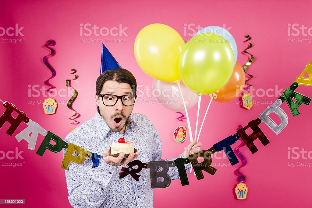 Surprised Nerdy man holding gift and multicolored balloons, Happy birthday! royalty-free stock photo