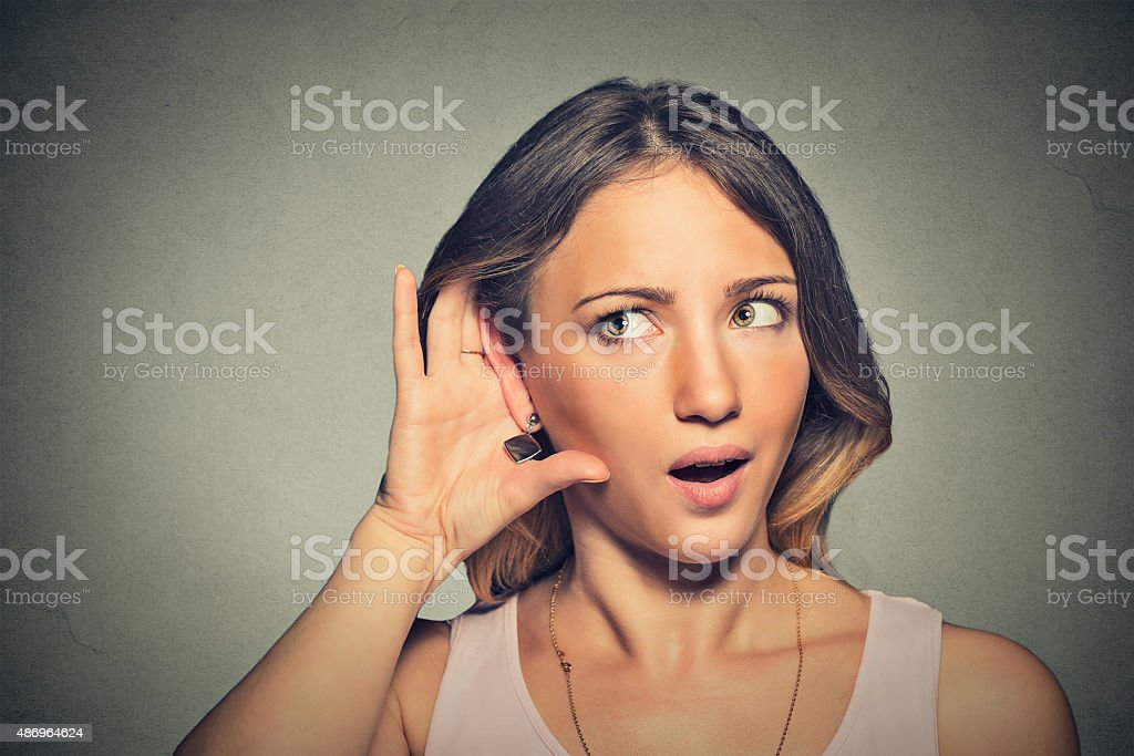 surprised nosy woman hand to ear gesture carefully listening stock photo