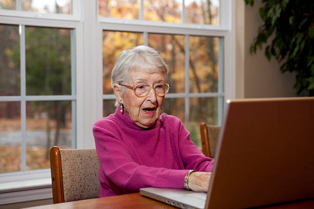 Surprised or Shocked Senior Woman, Grandmother at Computer  shocked computer stock pictures, royalty-free photos & images