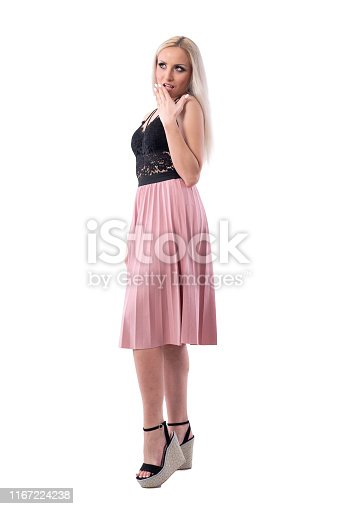 Surprised or shocked young woman with hand covering mouth looking up. Full body isolated on white background.