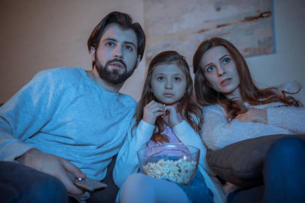 überrascht, eltern und tochter film auf sofa mit popcorn - mädchen night snacks stock-fotos und bilder
