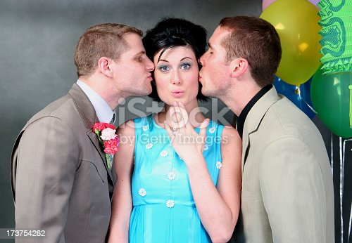 A pretty high school senior girl looks surprised as she gets a peck on each cheek by two good-looking boys.