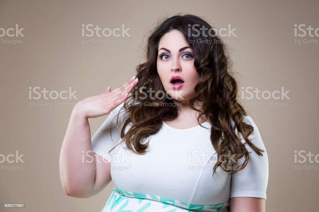 Surprised plus size fashion model, fat emotional woman on beige background, overweight female body stock photo