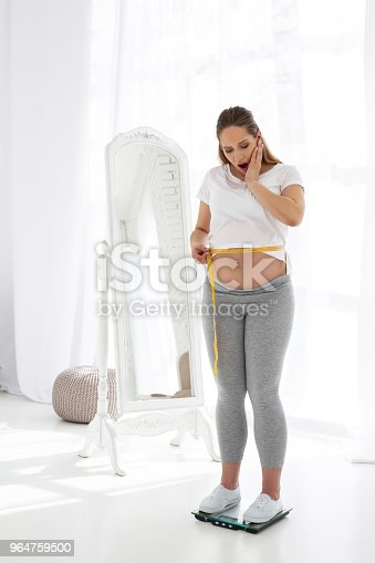 Surprised Pregnant Woman Measuring Size Stock Photo & More Pictures of Abdomen