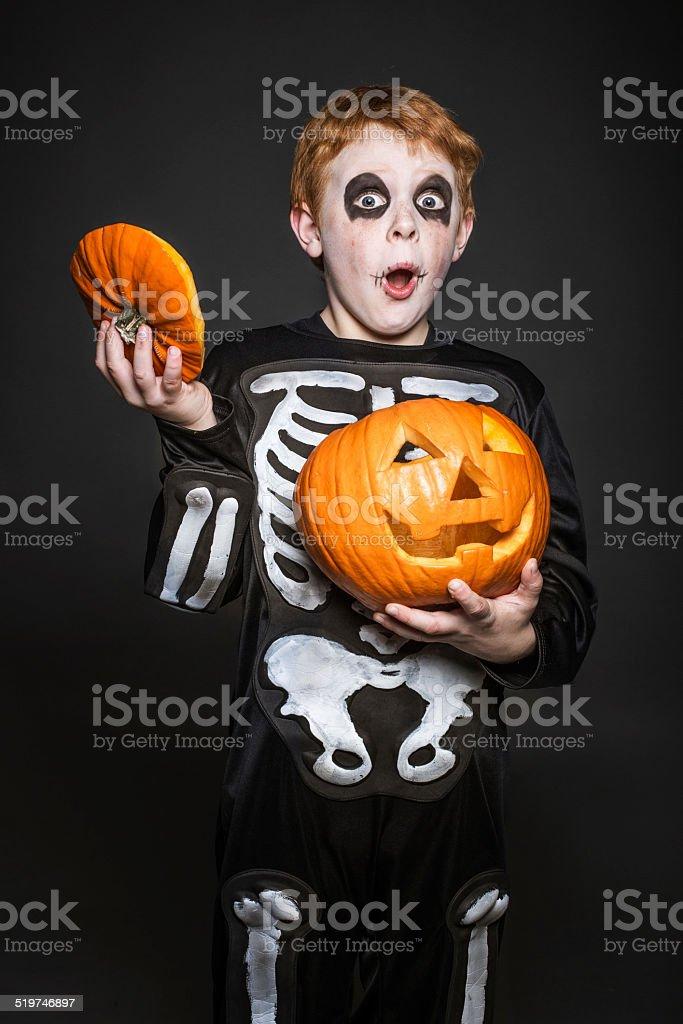 Surpris Cheveux roux enfant en costume tenant une citrouille d Halloween  photo libre de droits fcf16d47c0a