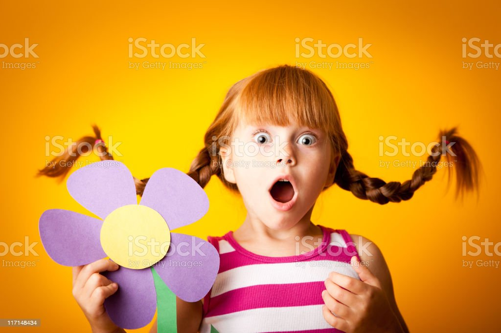 Surprised, Red-Haired Girl with Upward Braids and Oversized Flower royalty-free stock photo