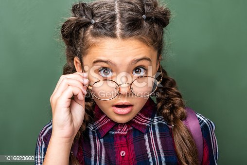 1016623732istockphoto surprised schoolchild looking at camera above glasses near blackboard 1016623660