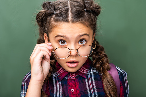 1016623732 istock photo surprised schoolchild looking at camera above glasses near blackboard 1016623660