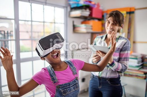 istock Surprised schoolgirl wearing VR headset by teacher 996979508