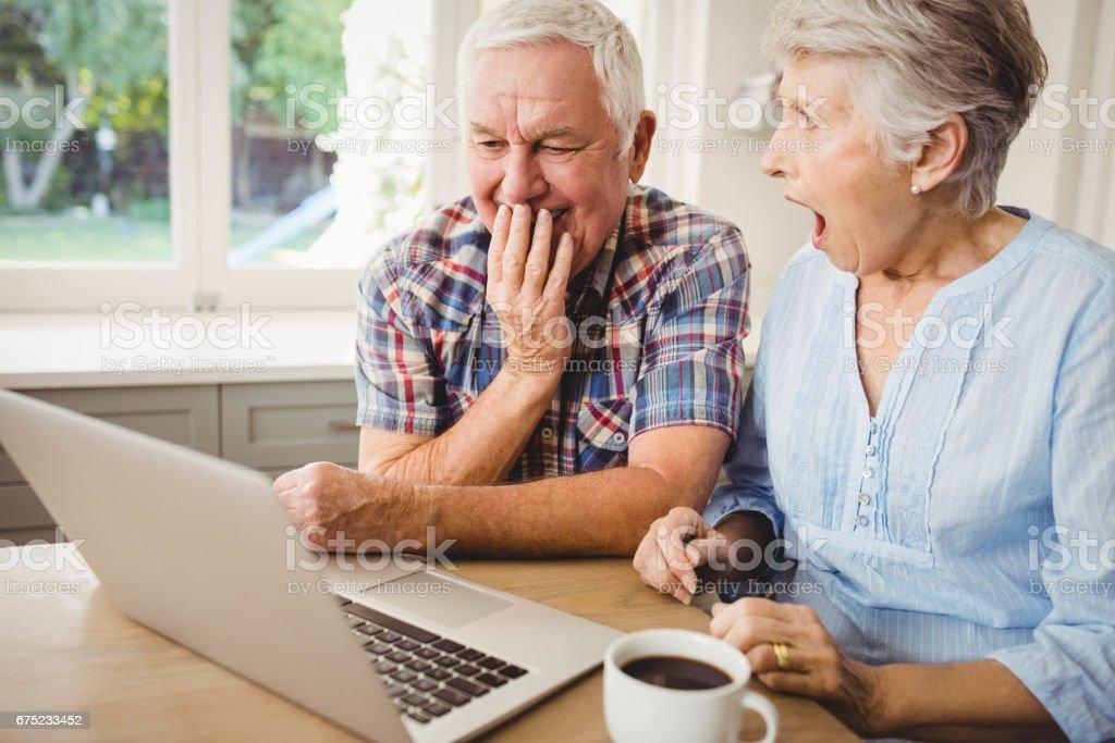 Surprised senior couple using laptop royalty-free stock photo