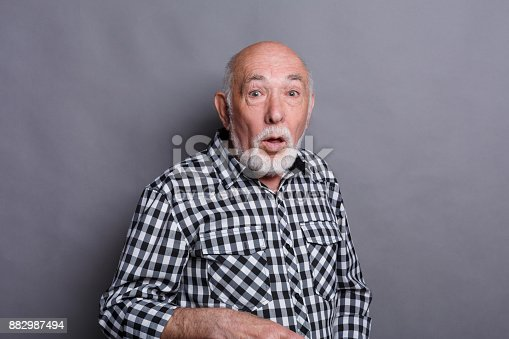 Surprised senior man in casual checkered shirt grimacing at gray studio background with copy space. Shok and excitement concept