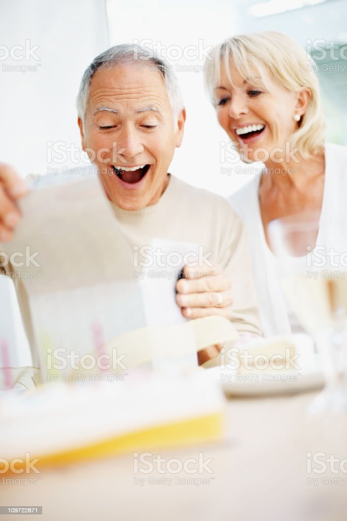 Surprised senior man with woman opening gift on birthday royalty-free stock photo