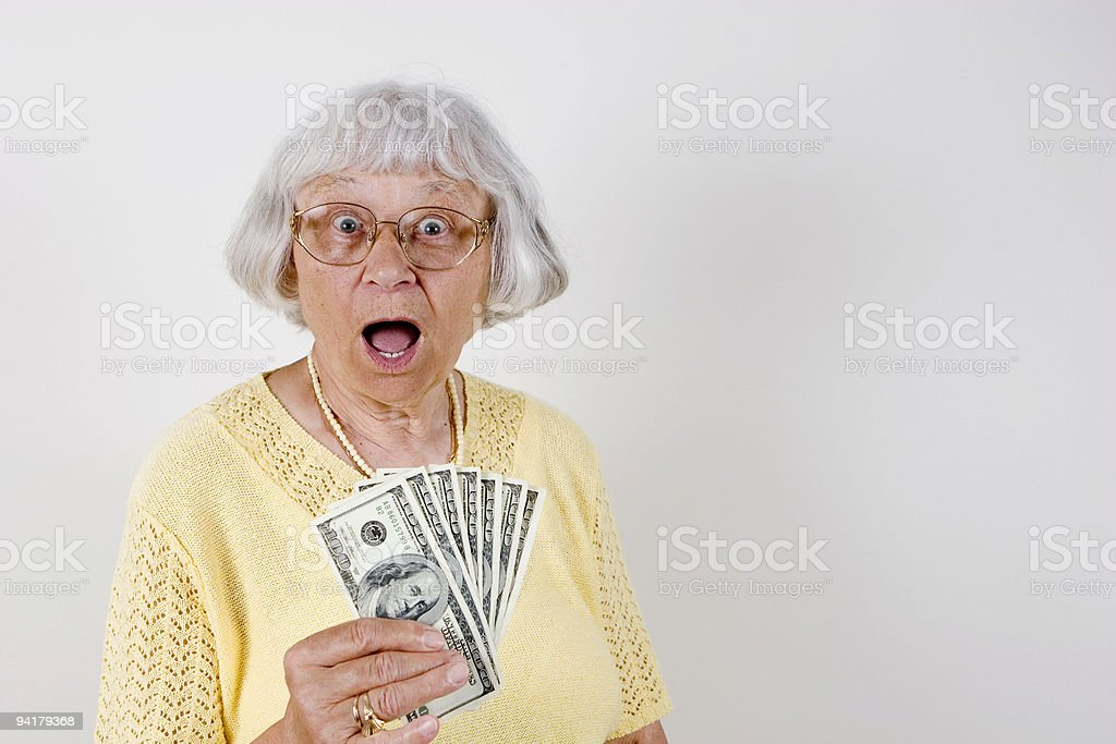 A surprised senior woman holding $100 bills stock photo