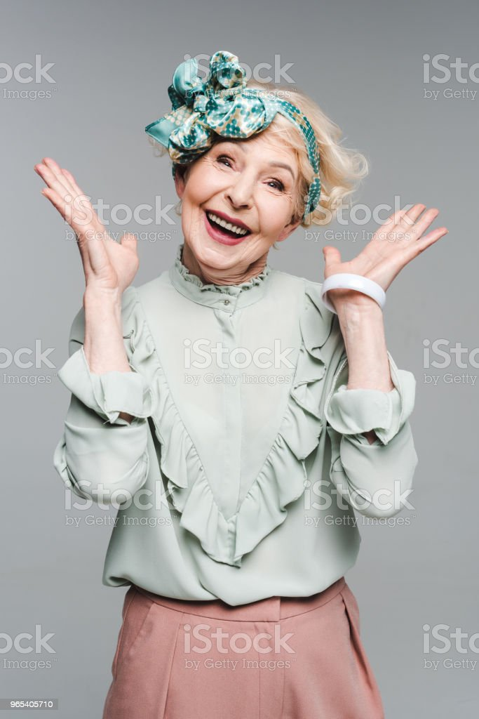 surprised senior woman in stylish clothes isolated on grey royalty-free stock photo