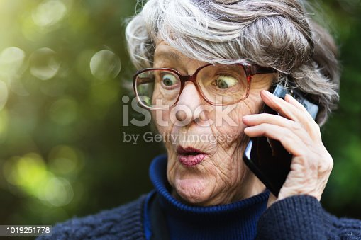 A shocked old lady in spectacles looks surprised and happily shocked as she talks or listens (probably to scandalous gossip) on her mobile phone in her garden.