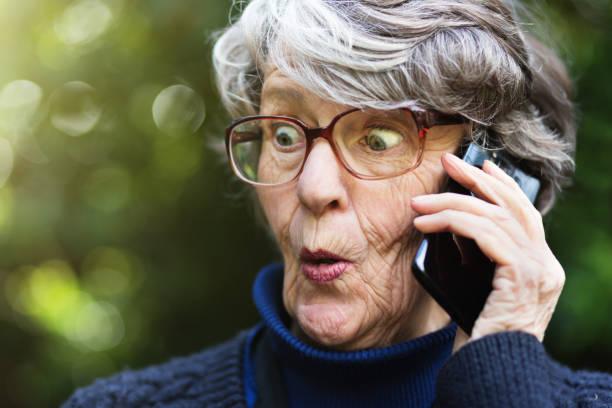mujer senior sorprendida escuchando exterior teléfono - cotilleo fotografías e imágenes de stock