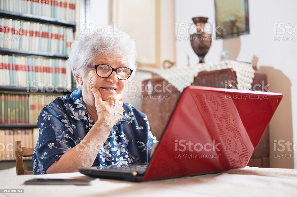 Surprised senior woman looking at laptop. stock photo