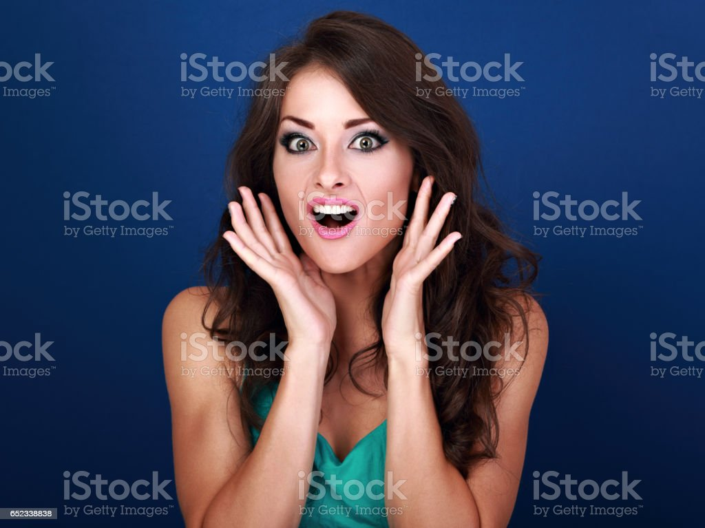 Surprised shock makeup woman with opened mouth and big eyes with hands at face on blue background. Closeup bright portrait stock photo
