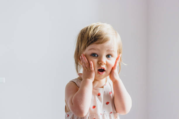 überrascht schockiert kind kleinkind mädchen mit händen auf den wangen isoliert auf leichtem hintergrund - toddler stock-fotos und bilder
